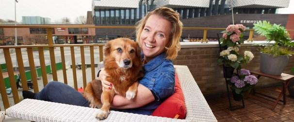 Vrouw met hond op balkon